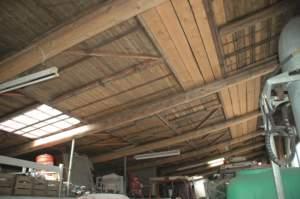 Porte di capannoni e stalle crollati per il terremoto sono diventati il tetto del magazzino ricambi provvisorio.
